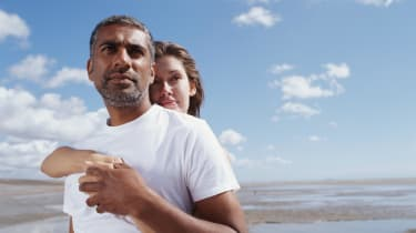 A couple on the beach look pensively at the horizon.