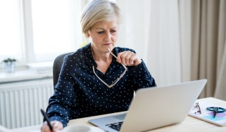 Woman with laptop working in home office.