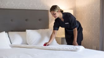 A housekeeper makes a bed in a hotel.