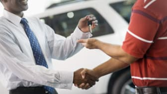Salesman Giving Man Keys to New Car
