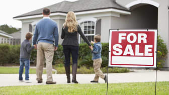 Family with two boys (4 and 6 years) standing in front of house with FOR SALE sign in front yard.Focus on sign.
