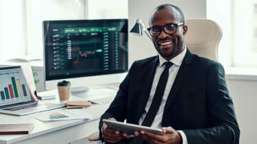 A smiling fund manager sits in front of multiple computers showing investment information