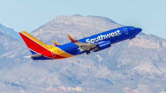A Southwest Airlines plane lifting off, with mountains in the background