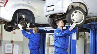 Mechanics working on vehicles in a garage