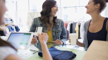 Laughing women paying at shop counter