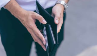 Man standing holding black wallet empty of money