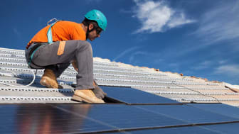 picture of man installing solar panels on a roof