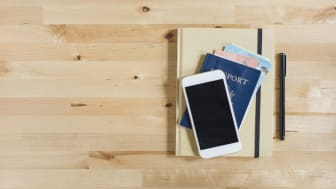 A cell phone atop a passport and travel journal