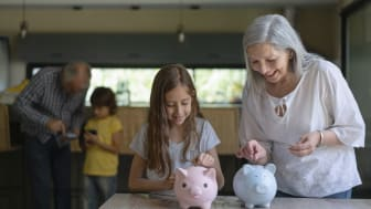 A grandmother and a granddaughter putting money into two piggybanks.