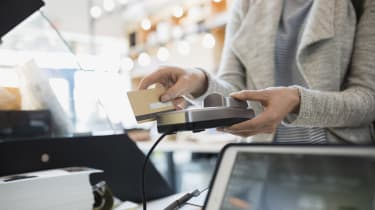 Customer paying at credit card reader in market