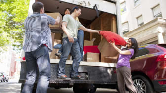 adult friends moving boxes from back of moving truck,urban street