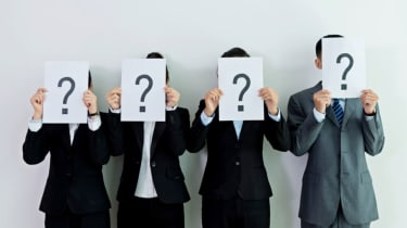 Four people in business suits hold up papers with questions marks on them in front of their faces.