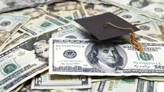 picture of graduation hat sitting on money