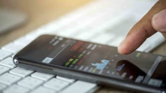 A person views a stock market chart on their phone.