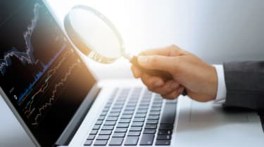 Businessman holding magnifying glass in hand, searching stock market data on laptop screen, investment trading concept