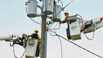 Caucasian workers in cherry pickers repairing power line