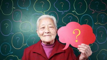 An older Asian woman holds a thought bubble with a question mark on it.