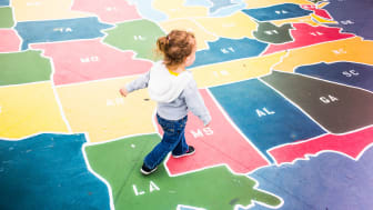picture of child walking across map of U.S. states on a playground