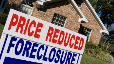 Price reduced and foreclosure sign in front of house for sale