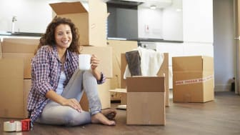 picture of woman drinking coffee around several moving boxes