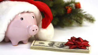 Piggy bank with Santa hat and money, christmas tree