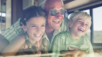 Senior man with grandchildren (7-10) looking out window of his RV, laughing