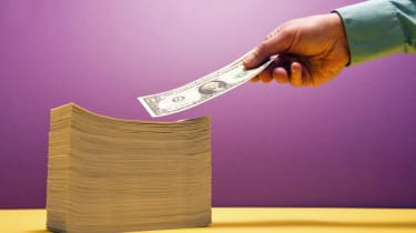 Man's hand placing 1 US dollar bill on large piles of bill on yellow shelf, purple background, selective focus