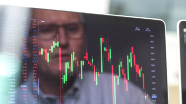 A man's face is reflected in a computer screen showing volatile stock movement.