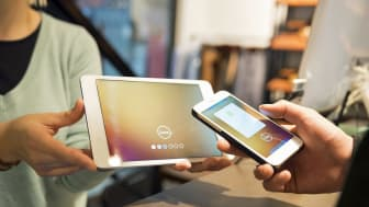 Close up of smart phone payment on tablet.