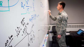 picture of an Air Force Academy cadet doing a complicated math problem on a classroom white board
