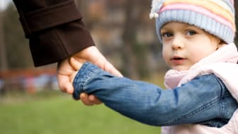 A small child holds her dad's hand.