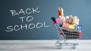 """picture of a small shopping cart filled with school supplies in front of a blackboard with """"back to school"""" written on it"""