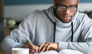 A young man takes notes as he studies a book.