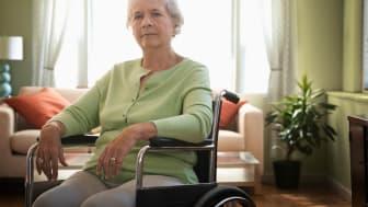 Senior woman sitting in wheelchair looking at camera