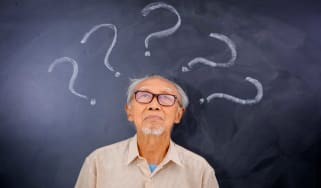 picture of elderly man with question marks written on blackboard above his head