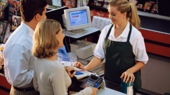 A grocery clerk helps a couple check out at the register