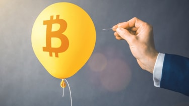 A balloon with a bitcoin symbol on it is in danger of being popped with a needle.