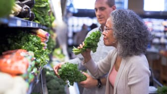 A multi-ethnic senior couple is in a grocery store shopping together. The woman is smelling some fresh herbs.