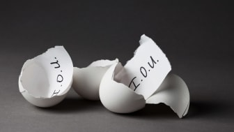 A broken egg shell with an IOU slip of paper