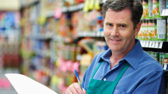 A supermarket manager in the aisle of a grocery store with paperwork