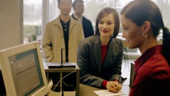 Bank teller assisting customers, focus on female leaning on counter
