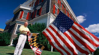 Senior man raises the U.S. flag and Maryland state flag at a Maryland beachfront home