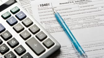 A calculator and a pen sit atop a 1040X tax form