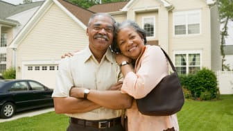 A senior couple smile at the camera in front of their home