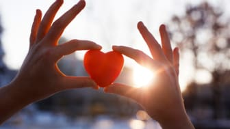 Two hands hold up a symbolic heart with the sun shining through