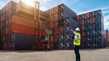 Hardhat worker pointing at shipping containers