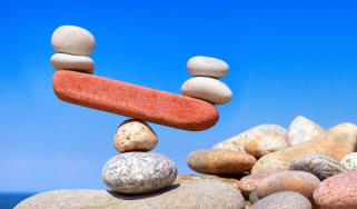 Rocks balance on a teeter-totter, with one end higher than the other.