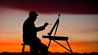 Silhouette of man painting a picture