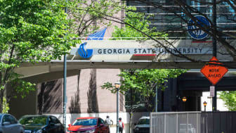 Georgia State University urban city campus with building hall sign and students walking in summer