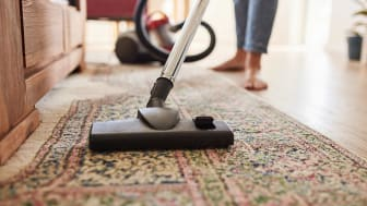 A woman vacuums a living room rug.